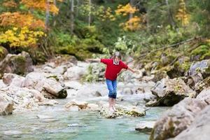 Smiling happy boy crossing wild mountain river jumping on stones