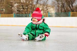 kleines Mädchen sitzt auf Eis mit Schlittschuhen nach dem Fall