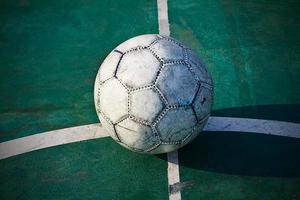 Old used football or soccer ball on cracked asphalt