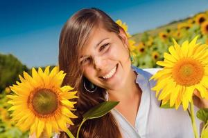 young beautiful woman between sunflowers