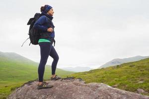 mulher de pé na rocha admirando a vista