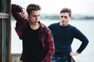 dos chicos están parados en un edificio abandonado en el lago