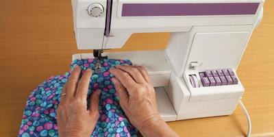 Sewing with sewer machine, hands and fabric photo