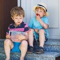Two little sibling boys eating fresh strawberries