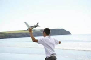 Boy flying toy airplane on beach photo