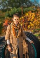 Smiling woman standing near wooden barrel in autumn outdoors