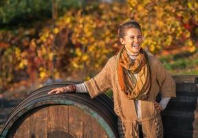 Portrait of smiling woman near wooden barrel in autumn outdoors
