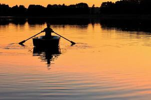 Mans silhouette  in the boat photo
