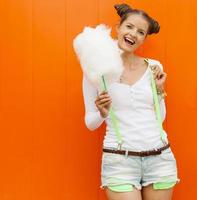 hermosa chica de moda con algodón de azúcar foto