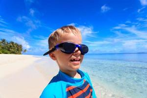 happy boy in swimming goggles at the beach