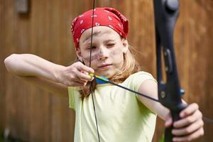 Girl archer with bow shooting to sport aim