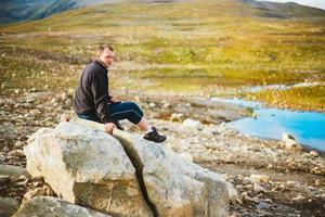 man zittend op steen in Noorse bergen