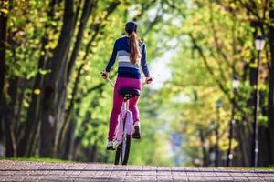 mujer joven, equitación, en bicicleta, en el estacionamiento