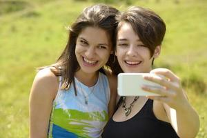 Two beautiful young women taking photos with phone outside