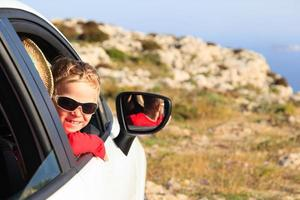 happy little boy travel by car in mountains