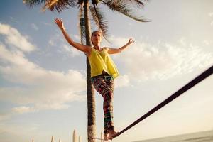 A teenage girl balancing on a rope beneath the sunny skies photo