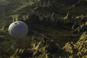 balloon glides over sun lit landscape with pike boulders photo