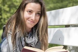 Young woman reading a book on a park bench photo