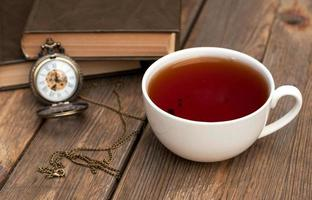 Cup of black tea and books on the wooden table photo