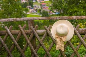 Female summer hat hanging on the wooden rustic fence