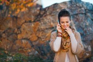 Mujer hablando por teléfono celular mientras camina en otoño al aire libre