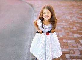 Retrato divertido niña alegre en vestido en el scooter