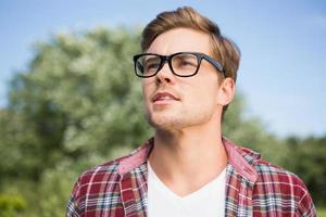 Handsome hipster thinking in the park