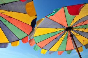 Rainbow umbrella on sky background photo
