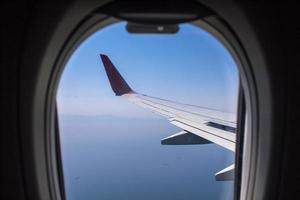 Airplane wing over the sky from window