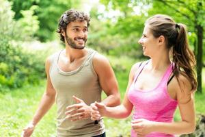 Smiling happy couple running in a park photo
