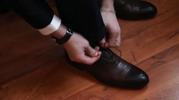 Nahaufnahme von Mannbein und Händen, die Schnürsenkel binden