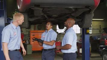 três mecânicos de automóveis olham para um carro juntos