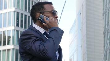 hübscher junger Geschäftsmann, der sein Büro mit einem Handy ausarbeitet: Smartphone; Mobiltelefon