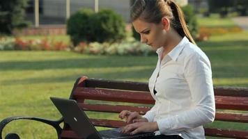 chica trabajando en la computadora portátil en el banco