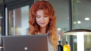 Beautiful girl working with her laptop in cafe video