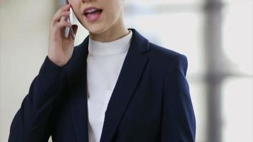 Businesswoman dialing and communicating on mobile phone video