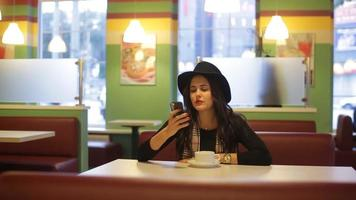 Young woman sitting in cafe and read message