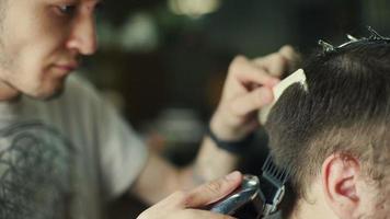 barbeiro cortando e modelando cabelos com aparador elétrico