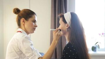 maquiador fazendo maquiagem para uma jovem