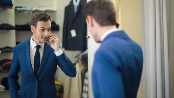 gutaussehender Mann im Bekleidungsgeschäft, der per Telefon spricht