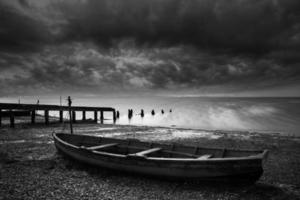 Old decayed rowing boats on lake with stormy sky photo