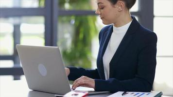 La empresaria usando un portátil mientras recibe una llamada en el escritorio