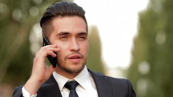 Young businessman talking on mobile phone video