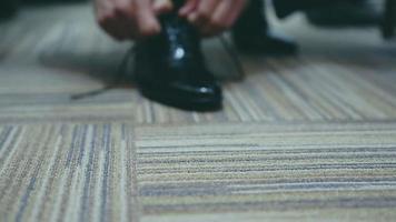 homem amarrando sapatos de couro envernizado. vestimenta formal e festiva. a câmera está se aproximando ou se afastando do objeto.