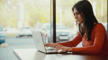 femme tapant sur ordinateur portable et souriant au café