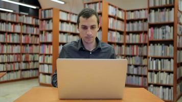 giovane uomo bello si siede e lavora al computer portatile