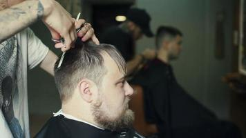 cabeleireira cortando cabelo de cliente sorridente em salão de beleza