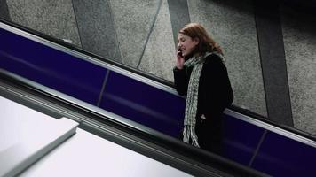 young woman talking to the mobile phone on escalators video