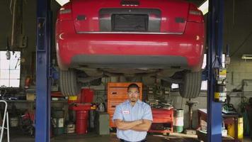 Retrato de mecánico de automóviles de pie en la tienda video
