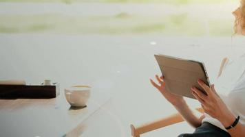 uma mulher em um café, bebendo café e trabalhando no tablet.